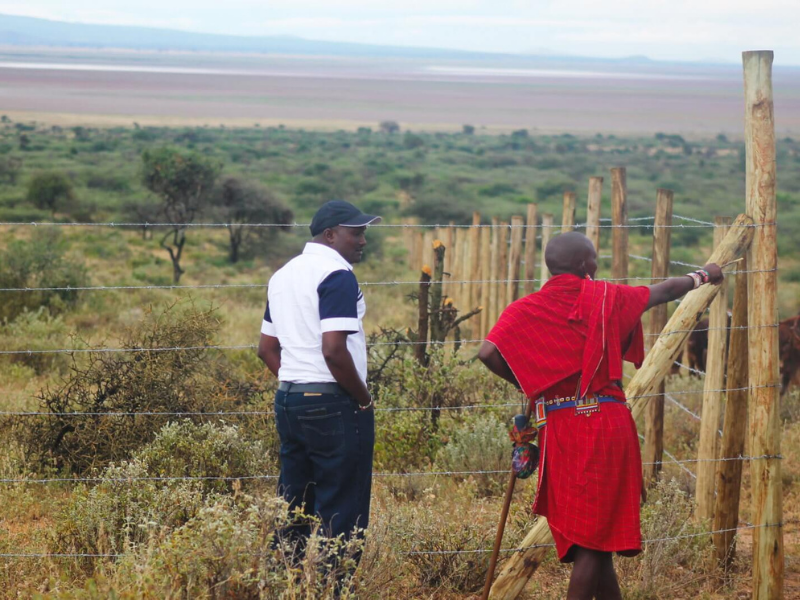 Two people standing in from of a traditional Maasai Olopololi plot